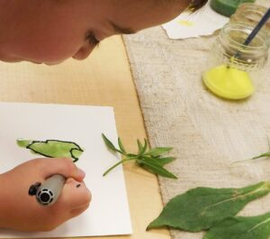 a young child painting leaves